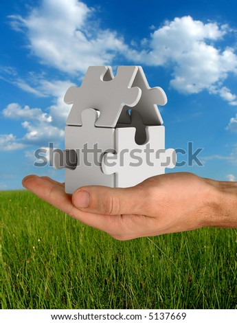 Puzzle home on hand - stock photo