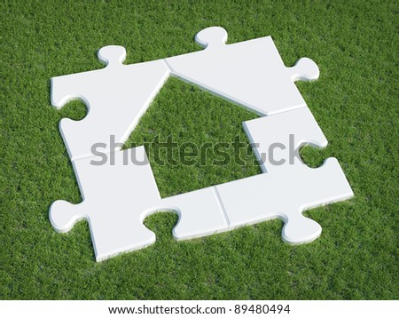 Puzzle house symbol on grass - stock photo
