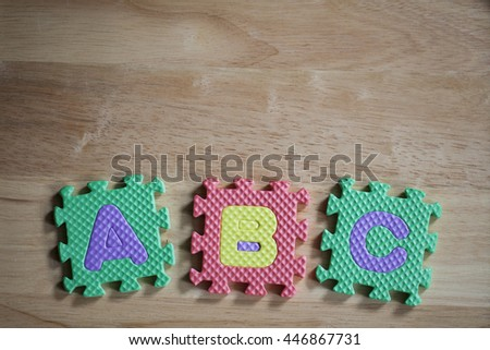 """Puzzle mats lettering over a wood background showing letters of the alphabet """"ABC"""" - stock photo"""