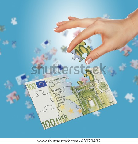 Puzzle of the euro banknotes and hands which it is collected. Symbol of business - stock photo