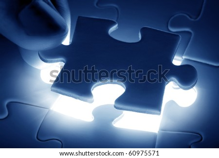 puzzle piece coming down into it's place - stock photo