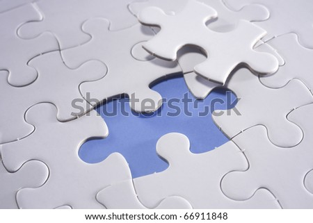 Puzzle piece next to the missing grid. - stock photo