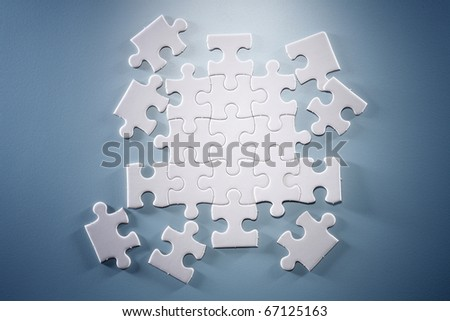 Puzzle pieces isolated on the blue background. - stock photo