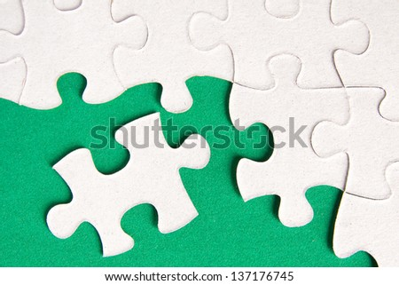 Puzzle pieces on green background close up. - stock photo
