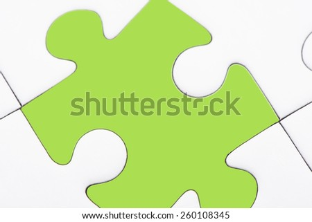 Puzzle pieces, one piece with green color texture. Conceptual image of connection, solution and business strategy. - stock photo