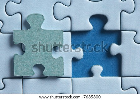 puzzle with a hole and the missing piece - stock photo