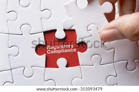 Puzzle with word regulatory and compliance - stock photo