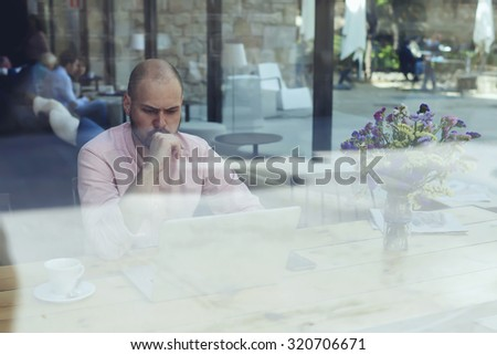 Puzzled and concerned male freelancer or student look to net-book, worried and thoughtful businessman or entrepreneur sitting front open laptop computer in modern coffee shop interior in urban setting - stock photo