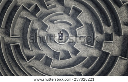 Puzzled businessman standing in center of labyrinth - stock photo