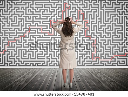 Puzzled businesswoman looking at a maze on a wall - stock photo