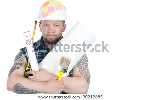 Puzzled caucasian manual worker with different working instruments and blueprint roll, isolated over a white background - stock photo