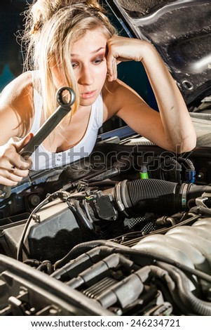 Puzzled girl with wrench in hand trying to repair their own broken car working on the transmission. - stock photo