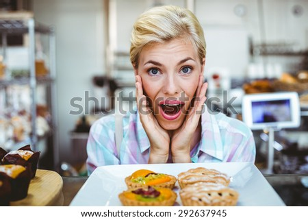 Puzzled pretty woman looking at a fruit pie at the bakery - stock photo