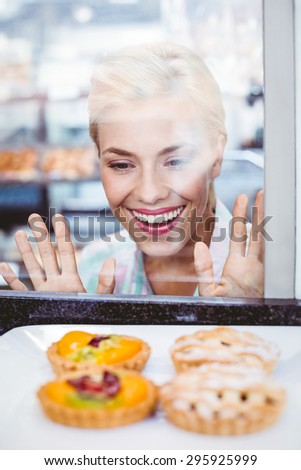 Puzzled pretty woman looking at a fruit pie at the bakery through the glass - stock photo