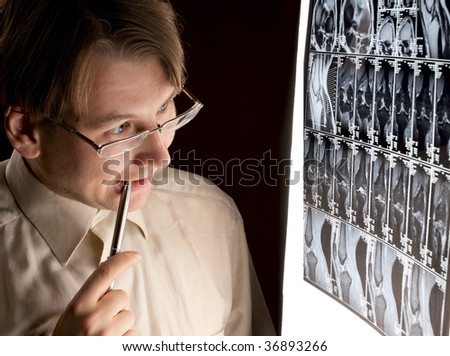 Puzzled radiologist looking at MRI in dark room - stock photo