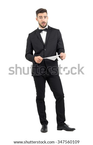 Puzzled shocked young groom expression after reading contract.  Full body length portrait isolated over white studio background.