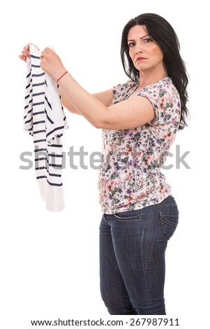 Puzzled woman holding new shirt isolated on white background
