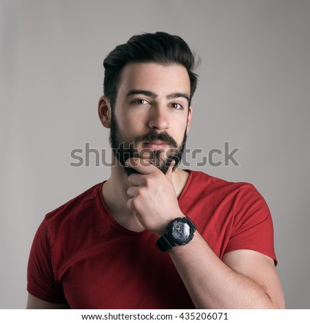 Puzzled young man stroking touching beard looking at camera over gray background