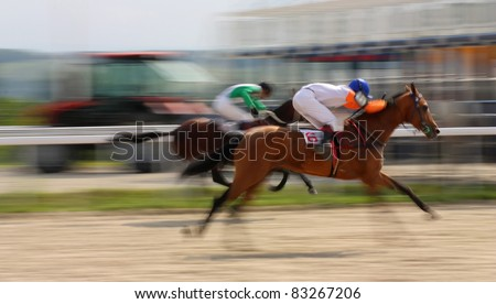 PYATIGORSK, RUSSIA-AUGUST 21: Jockeys (L - R) Imran Mardanov,Yuri Tihonov and akhal-teke stallion Shanda race for the prize of Omar Iskandarova  on August 21, 2011 in Pyatigorsk, Caucasus, Russia. - stock photo
