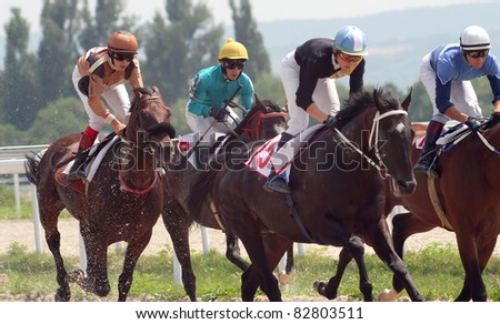 PYATIGORSK, RUSSIA -AUGUST14: Jockeys (L - R) Rasul Panjokov, Shamil Hatkov, Shamil Guseinov and Imran Mardanov race for the prize of Dnya Stroitela on August 14,2011 in Pyatigorsk, Caucasus, Russia.