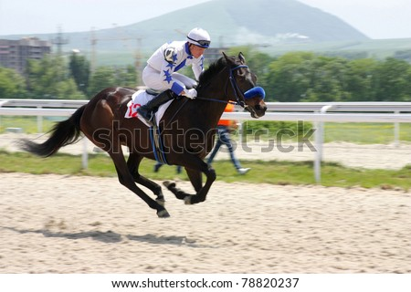 PYATIGORSK, RUSSIA - JUNE 5:Jockey Vlad Parfuta crosses the finish line first in a horse race for the prize of the Kabardino-Balkarii on June 5, 2011 in Pyatigorsk, Caucasus, Russia.