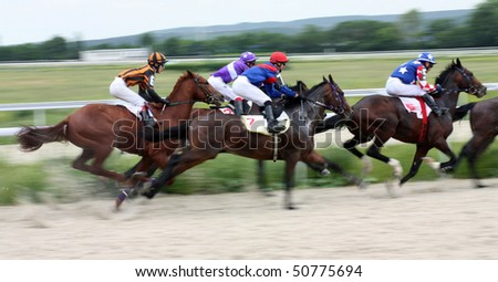 PYATIGORSK, RUSSIA - JUNE 14: Jockeys with their horses come down the home stretch on June 14, 2009 in Pyatigorsk, Caucasus, Russia. - stock photo