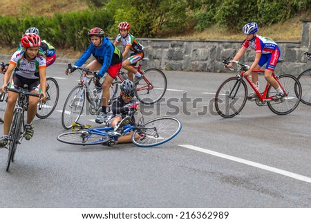 Pyatigorsk , Russia - September 7, 2014: Training young cyclists on the streets of Pyatigorsk in the rainy overcast day. Falling cyclist during the competition on an urban street.   cyclist.