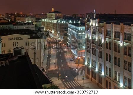 Pyatnitskaya street with road, bike paths and sidewalks at night in Moscow. Text on wall - bank - stock photo