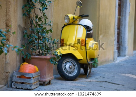 PYENZA, ITALY - SEPTEMBER 22, 2017: Box with orange pumpkins, green plant and yellow scooter at the wall of the old house