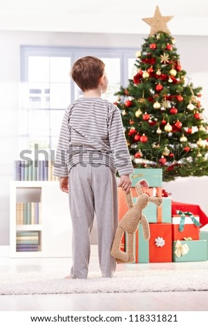 Pyjama boy holding toy bunny looking at christmas tree and gifts in morning. - stock photo