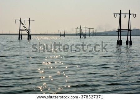 Pylons and building flooded by lake near Lokbatan, Azerbaijan. A recently flooded landscape shows signs of its previous state in Lokbatan, 15km south west of Baku