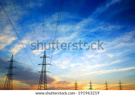 Pylons and power lines at sunset with vibrant sky,clouds and sun - stock photo