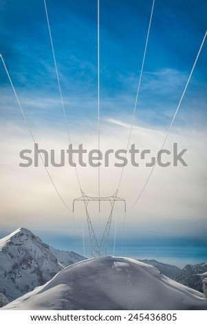 Pylons covered with snow in the high mountains carry energy downstream - stock photo