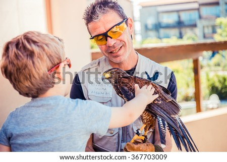 PYLOS, GREECE, 20 JUNE: boy caress a hawk holding by security, Greece - stock photo
