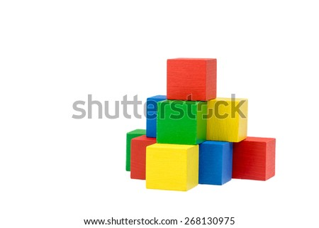 Pyramid built from variously wooden colorful cubes on an isolated white background. The red cube is on the top of the pyramid. Side view. - stock photo