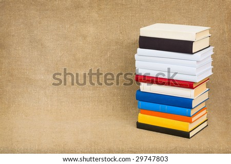 Pyramid from books with color covers on a canvas - stock photo