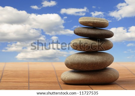 Pyramid from five smooth round grey stones on a heavenly background - stock photo