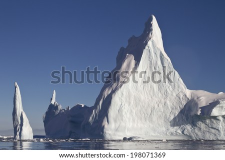 Pyramid iceberg with two peaks in Antarctic waters - stock photo