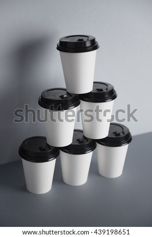 Pyramid made from six white take away paper cups with closed black caps, isolated on simple gray background, top view - stock photo