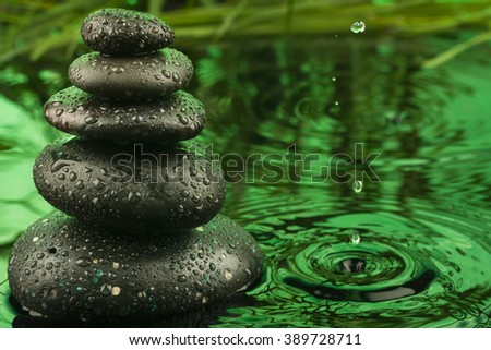 Pyramid made of stones and a drop in the green water, as background - stock photo