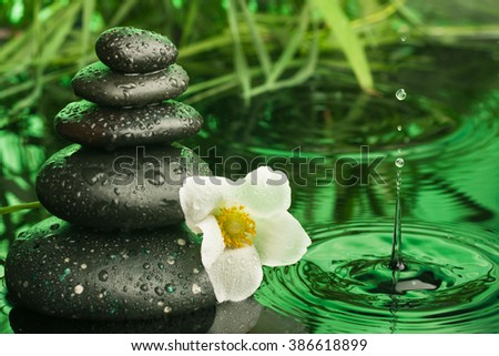 Pyramid of black stones and white flower,  as background - stock photo