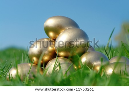 Pyramid of golden eggs in grass over blue sky - stock photo