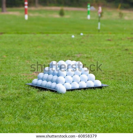 Pyramid of golf balls on driving range. Shallow depth of field. Focus on the pyramid of golf balls. - stock photo