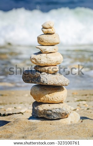 Pyramid of Pebbles against of the Sea - stock photo