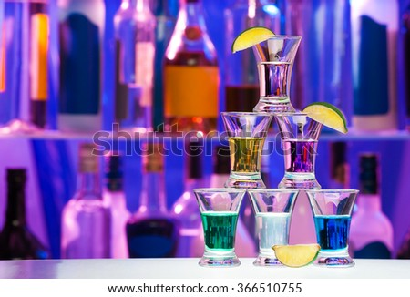 Pyramid of shot glasses with drinks and lime - stock photo
