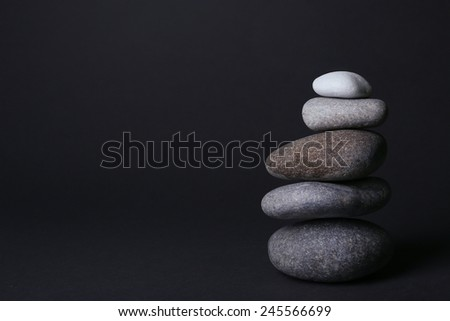 Pyramid of spa stones on dark background - stock photo