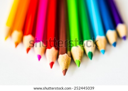Pyramid of the colored pencils on paper. Focus on the brown pencil, in hard tones - stock photo