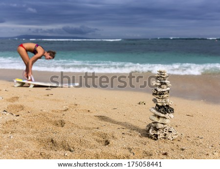 Pyramid of the corals on the ocean shore. Beautiful young girl fixes surfer board on the foot - stock photo