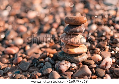 Pyramid of the sea pebbles / Rocky bright background with a place for an inscription - stock photo