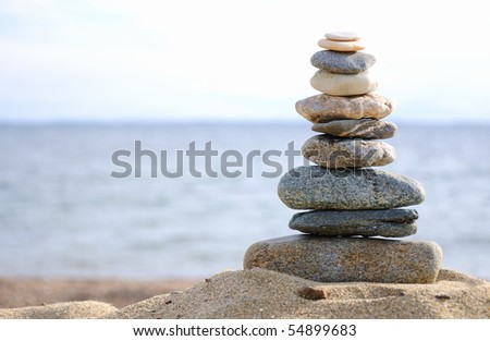 Pyramid of the small pebbles on the beach - stock photo